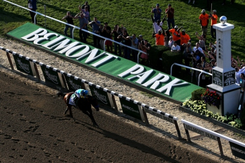 ELMONT, NY - JUNE 06:  American Pharoah #5, ridden by Victor Espinoza, crosses the finish line to win the 147th running of the Belmont Stakes at Belmont Park on June 6, 2015 in Elmont, New York.  (Photo by Mike Stobe/Getty Images)
