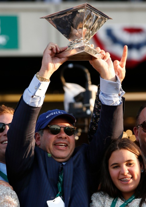 Ahmed Zayat holds up the Triple Crown Trophy after American Pharoah won the 147th running of the Belmont Stakes horse race at Belmont Park, Saturday, June 6, 2015, in Elmont, N.Y. American Pharoah is the first horse to win the Triple Crown since Affirmed won it in 1978.(AP Photo/Kathy Willens)